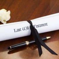 A scroll of a Last Will & Testament, tied with a black ribbon on a mahogany desk, with a white rose and pen. Good copy space